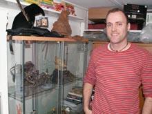 Lars foran sin montre med lækkert merchandise - bemærk Harry Potter-hattene ovenpå montren