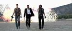 De tre bandemedlemmer går på en sej måde væk fra en eksplosion