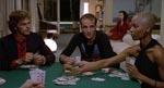 Imens Alex forsøger at komme i bukserne på Lisa, spiller Ricky (i midten, spillet Giovanni Lombardo Radice) kort med Howard (Gabriele Di Giulio), Glenda (Marie Claude Joseph) og Tom (offscreen). I baggrunden kigger Gloria (Lorraine De Selle) på.