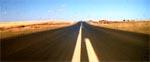 Landevejen set fra Max' Interceptor med en lille jagtet motorcykelskikkelse i det fjerne