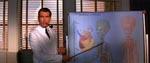 Pierce Brosnan som kikset videnskabsmand i en scene, der er et glimrende eksempel på filmens genrepastiche