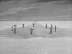 Mændene, der kan ane tingen igennem isen, stiller sig i udkanten af den og i denne stemningsfulde scene, går det op for dem, at tingen i isen er cirkulær